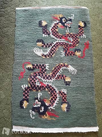 Grüner Teppich mit roten Drachen