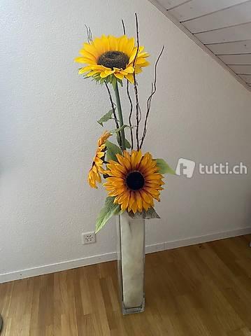 Glasvase mit künstlichen Sonnenblumen